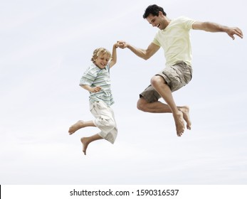 Low angle view of father and son jumping