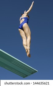 Low angle view of a female swimmer jumping on diving board against clear blue sky