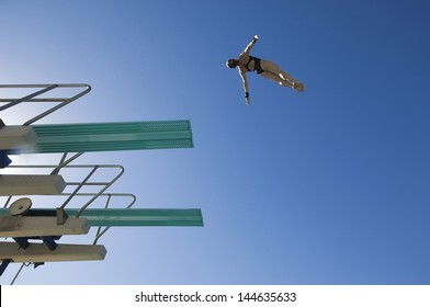 Low angle view of a female swimmer preparing to dive from diving board against clear blue sky