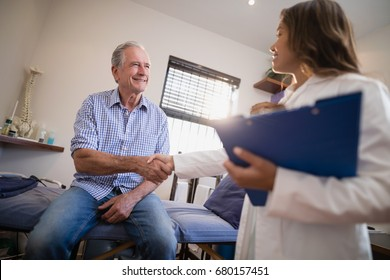 Low angle view of female therapist and senior male patient shaking hands at hospital ward