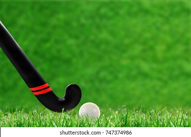 Low angle view of field hockey stick and ball on field grass and deliberate shallow depth of field on background with copy space.