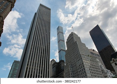 Low Angle View of Fifth Avenue Skyscrapers in Middle Upper Manhattan with Cloudy Blue Sky in Background, New York City, New York, USA