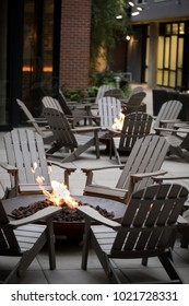 Low angle view of a fire pit surrounded by a circle of Adirondack chairs, with another campfire and apartment building in the dark background