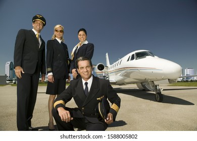 Low angle view of flight crew standing next to airplane on tarmac