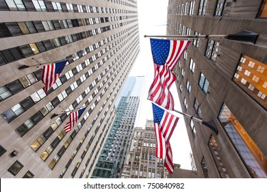 Low angle view of fluttering USA flags on a skyscraper in Midtown Manhattan, New-York.