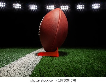 Low angle view of a football on a tee on black background under lights