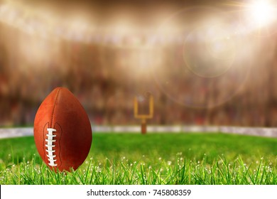 Low angle view of football on field grass and deliberate shallow depth of field on brightly lit stadium background with copy space. Ready for kick off or field goal.