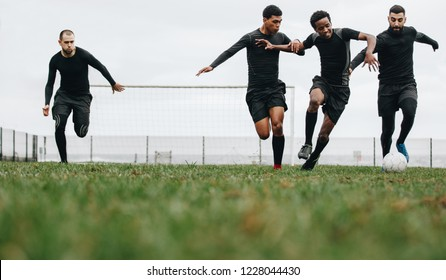 Low angle view of footballers playing on the field running for the ball. Group of men running for possession of ball while playing football.