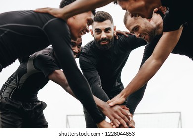 Low angle view of footballers talking about the game plan standing in a huddle. Soccer players holding their hands standing in a huddle and cheering themselves up.