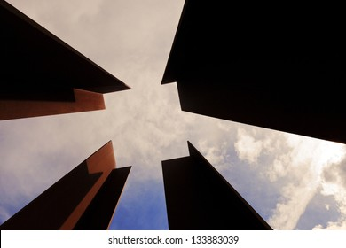 Low angle view of four columns that together create a negative space in the shape of a square, on the background of cloudy sky at the afternoon.