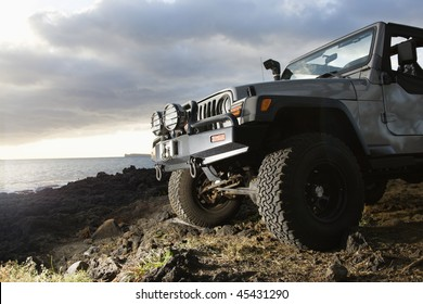 Low angle view of front of SUV on a rocky beach. Horizontal format.