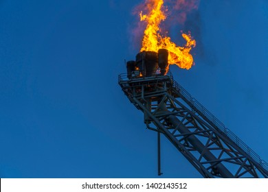 Low angle view of gas flare burning on the oil rig platform in the middle of the sea with blue sky.