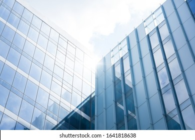 Low angle view of generic modern office skyscrapers ,high rise buildings with abstract geometry glass facades on a bright sunny day . Concepts of finances and economics background.