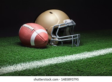 A low angle view of a gold football helmet with a football on a grass field with stripe and dark background