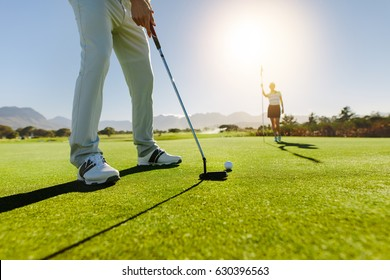 Low angle view of golfer on putting green about to take the shot. Male golf player putting on green with second female player in the background holding the flag.