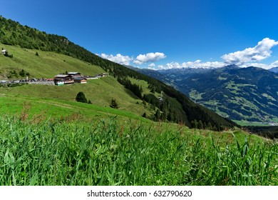 Low angle view of green meadow and alpine village with high mountains under blue sky. Austria, Tirol, Zillertal, Zillertal, High Alpine Road