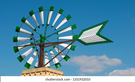 Low angle view, of a green and white Mallorcan windmill against a clear blue sky.