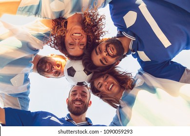 Low angle view of a group of football fans wearing jerseys, gathered in a circle and holding a ball with their heads