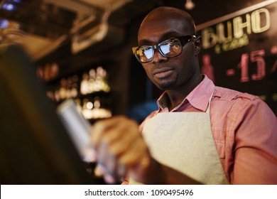 Low angle view of handsome black male waiter in glasses using POS system while working in restaurant