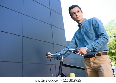low angle view of handsome young man standing with bike and looking away