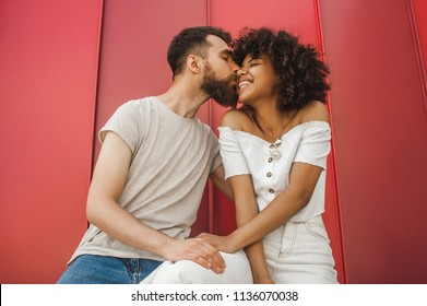 low angle view of handsome young man kissing happy african american girlfriend
