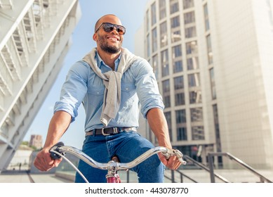 Low angle view of handsome young Afro American man in casual clothes and sun glasses riding his bike and smiling
