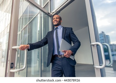 Low angle view of handsome young Afro American businessman in classic suit holding a laptop and smiling while leaving the office building