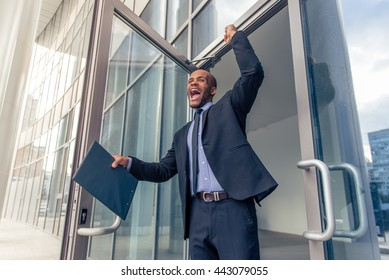 Low angle view of handsome young Afro American businessman in classic suit holding folder, keeping fist up and screaming with happiness while leaving office building