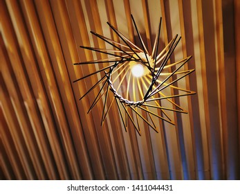 Low Angle View of Hanging Illuminated Light Bulb on Wooden Planks Ceiling