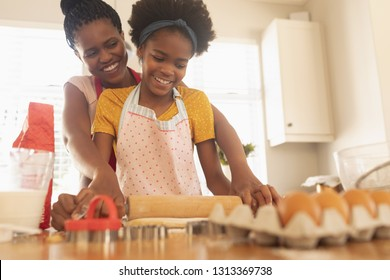 Low angle view of happy African American mother and daughter baking cookies in kitchen at home