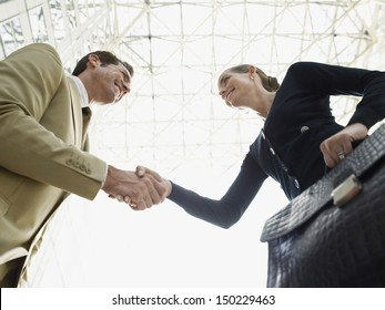 Low angle view of happy businessman and businesswoman shaking hands against ceiling
