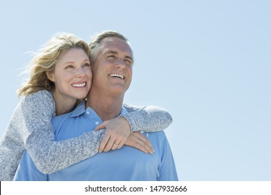 Low angle view of happy mature woman embracing man from behind while looking away against clear sky