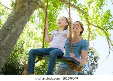 Low angle view of a happy mother swinging daughter at the park