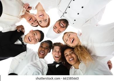 Low Angle View Of Happy Restaurant Staff Standing Against White Background