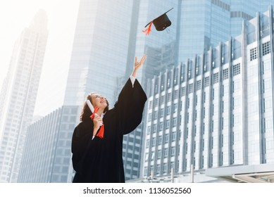 Low angle view of happy young student graduate in black gown & hold diploma certificate, throwing up her graduation cap in the air and celebrating. Finishing school and find a job. Congratulations!