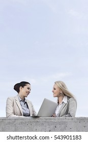 Low angle view of happy young businesswomen with laptop discussing while standing on terrace against sky