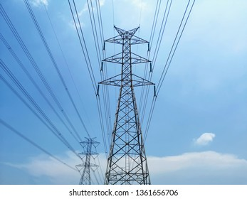 Low Angle View of High Voltage Tower and Power Lines Against Blue Cloudy Sky