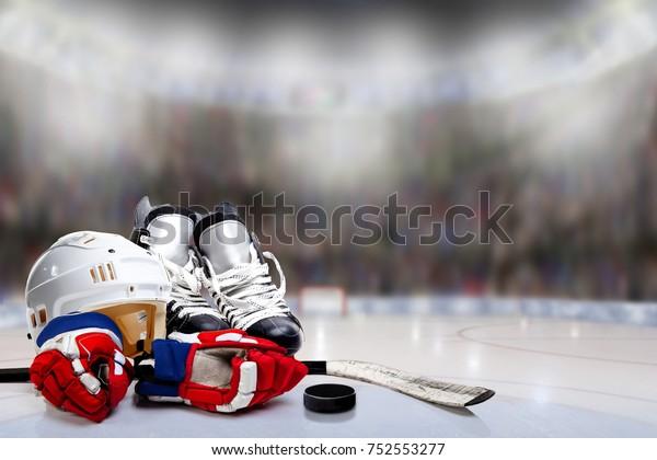 Низкоугольный вид хоккейного шлема, коньков, перчаток, палки и шайбы на льду с намеренной неглубокой глубиной резкости на ярко освещенном фоне стадиона и копировального пространства.