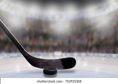 Low angle view of hockey stick and puck on ice with deliberate shallow depth of field on brightly lit stadium background and copy space.