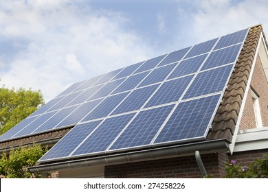 Low angle view of house roof covered with solar panels against sky