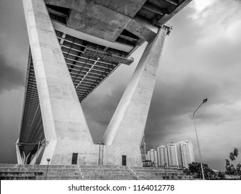 Low angle view of huge and stately bridge with strong pillar with cloudy sky and tower in the background, urban and futuristic concept, Bhumibol Bridge, Bangkok, Thailand