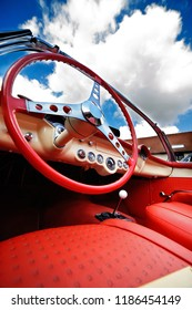 Low angle view from interior of beautiful classical convertible car. Red leather seats and steering wheel in foreground. Bright sky in background.