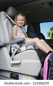 Low angle view of little schoolgirl safely buckled into booster seat