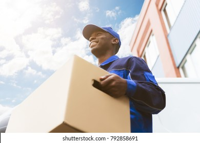 Low Angle View Of Loader Man Standing Near The Van Holding Cardboard Box