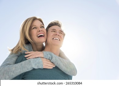 Low angle view of loving man giving piggyback ride to happy woman against clear sky