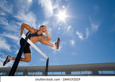Low angle view of a male athlete jumping over the hurdle with the background of sun flare and blue sky.