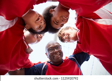 Low Angle View Of Male High School Soccer Players And Coach Having Team Talk