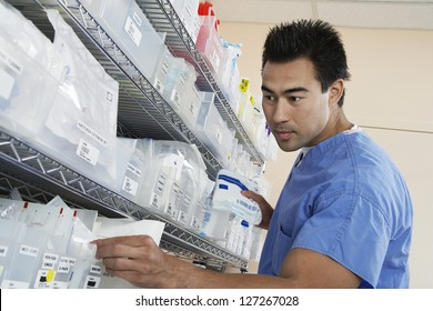 Low angle view of a male pharmacist in uniform keeping medical supplies at retail pharmacy drug store