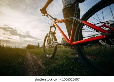 Low angle view of man cyclist standing with his bike at country road getting ready to ride. Bicycle traveling, healthy lifestyle and activity concept