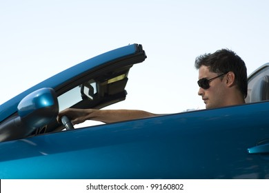Low angle view of a man driving his convertible car
